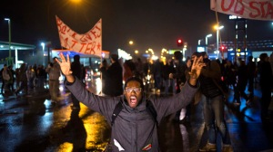 A protester, demanding the criminal indictment of a white police officer who shot dead an unarmed black teenager in August, shouts slogans while stopping traffic while marching through a suburb in St. Louis, Missouri November 23, 2014. (Reuters/Adrees Latif)